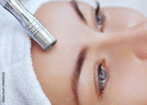 The cosmetologist makes the procedure Microdermabrasion of the facial skin of a beautiful, young woman in a beauty salon.Cosmetology and professional skin care. - 196842502