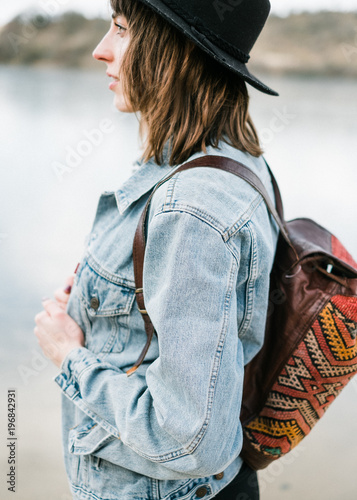 Color close up portrait of a young woman with dark hair and a hat. She's sitting outside and is a hipster type and is wearing a denim jacket, hat and colorful backpack
