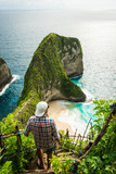 Man standing on a rock ladder at the edge of a cliff on Nusa Penida island - 196846129