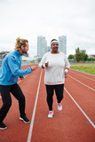 Young sporty female training to run before marathon and following instructions of her personal trainer