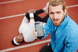 Young trainer showing results of his trainee in smartphone after workout