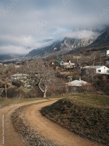 Foto op Canvas Bleke violet Village landscape in a spring day with road leading to mountain