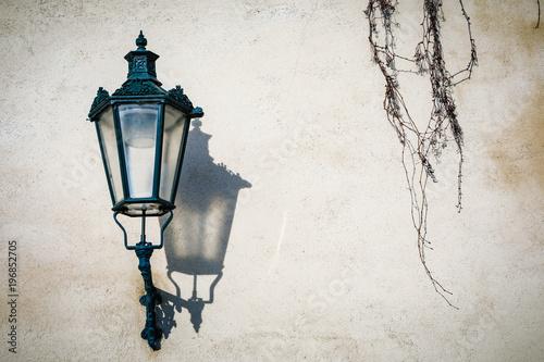 Sticker Antique lamp on a wall at natural lighting. Prague. Czech Republic