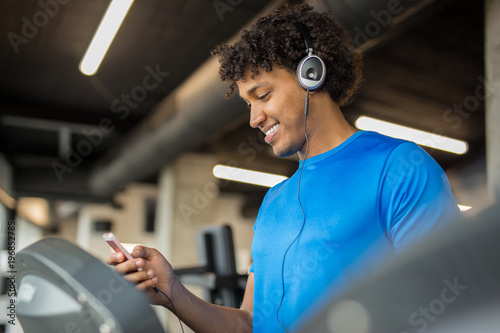 Handsome african american man working out at the gym while listening to music