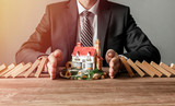 Close-up of a man stopping the wooden blocks from falling on house model. House insurance and security concept. - 196853104