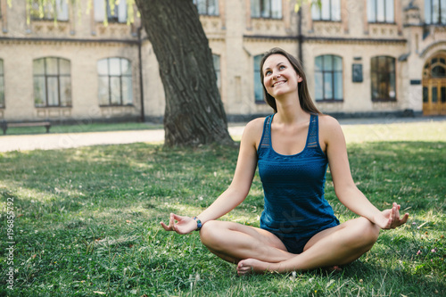 Fototapeta Young yoga woman practitioners yoga on nature.