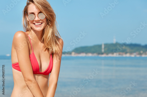 Outdoor shot of happy female rests at sea, poses against beautiful ocean or sea view with blue horizon, wears trendy shases and red bikini, gets tan on coastline. Summer time and spare time.