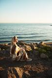 Blonde girl enjoying summer evening by seaside while sitting by water - 196861149