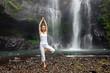 Woman practices yoga near Sekumpul waterfall in Bali, Indonesia - 196875128
