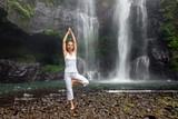 Woman practices yoga near Sekumpul waterfall in Bali, Indonesia
