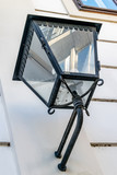 Old street lamp on the wall. The façade of a building is reflected in a lamp.