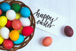 multicolored easter eggs in a wicker basket on a wooden white background, black inscription Happy Easter