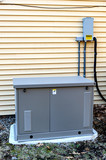 Residential generator on concrete pad, next to a house wall - 196882718