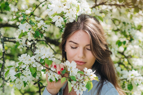 Woman near blooming apple tree - 196884555