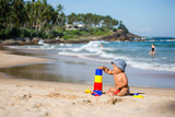 Kid plays with toys at the seashore in summertime - 196885371