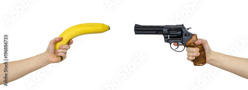 hand with a banana and a hand with gun isolated on white © vitaly tiagunov