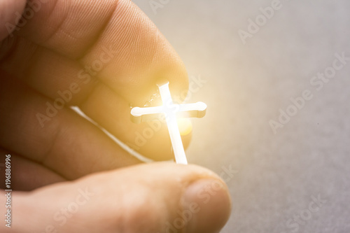 Silver cross in a hand - 196886996