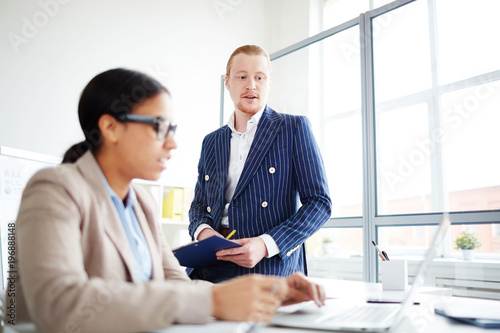 Businessman explaining to his secretary what document she has to typing on laptop