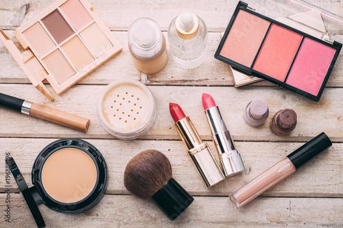 Zestaw dekoracyjnych kosmetyków. Puder do twarzy, korektor, cień do powiek, rumieniec, podkład. Drewniane tła.
