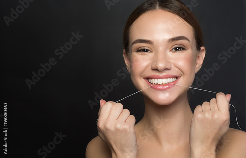 Leinwanddruck Bild Portrait of positive young woman who is taking care of her teeth. She is holding dental floss and laughing while looking at camera with joy. Isolated and copy space in left side. Dental health concept