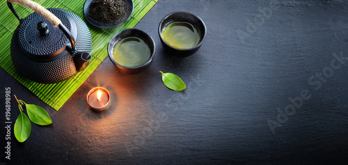 Fototapeta Green Tea In Iron Asian Teapot With Leaves And Bamboo Mat On Black Stone