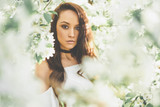 Beautiful young woman surrounded by flowers of apple-tree