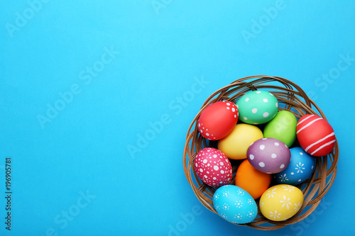 Colorful easter eggs in basket on blue background