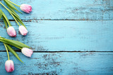 Bouquet of pink tulips on blue wooden table - 196905912