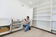 Man assembling kitchen cupboard using screwdriver