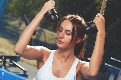 Portrait of young sporty woman exercising in outdoors gym at summer sunny day
