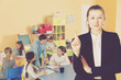 Strict female teacher standing foreground in classroom