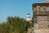 Buildings (formerly owned by the Bulgarian Orthodox Church) on St. Anastasia Island in the Burgas Bay of the Black Sea. Bulgaria. In the background lighthouse. - 196930564