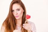 Flirty woman holding red wooden heart on stick - 196932180