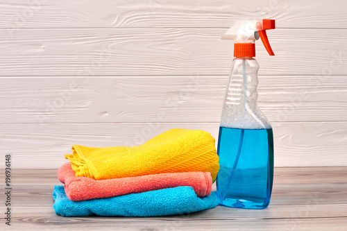 Cleaning spray bottle with plastic dispenser. Window cleaner and colorful rags o wooden background. Cleaning hacks and tips.