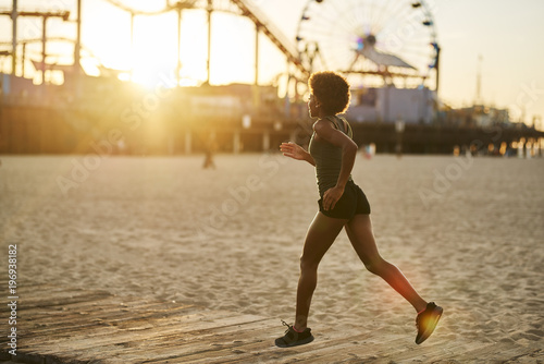 Aluminium Hardlopen athletic african american woman jogging on boardwalk at sunset