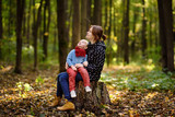 Little boy with his young mother enjoy stroll in the forest - 196948509