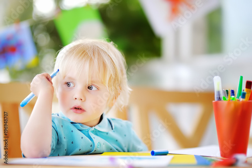 Cute little boy drawing and painting with colorful markers at kindergarten - 196948707
