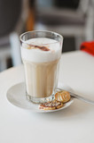 Latte macchiato, espresso with frothy milk, served in tall glass with cookies  on whtie table at coffee house - 196951186