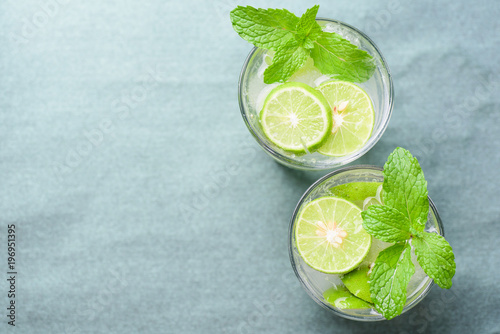 Fototapeta Glass of iced lemonade soda with slice lime and mint leaves, cold drink in summer