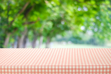 Empty table with pink and white tablecloth over blurred park nature background, for product display montage, spring and summer