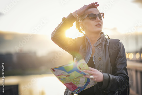 Confused female tourist in a foreign city using a map, trying to navigate herself around the city