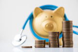 piggy bank with stethoscope and coins stack on white background - 196968387