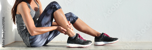 Running sport injury leg pain - runner woman runner hurting holding painful sprained ankle muscle. Female athlete with joint or muscle soreness and problem feeling ache banner panorama.