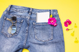 notebook, pen and flower in the blue jeans pocket