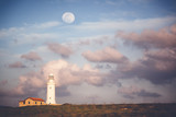 Beautiful scenery, a white lighthouse against a background of a blue sunset sky and the moon - 196986356