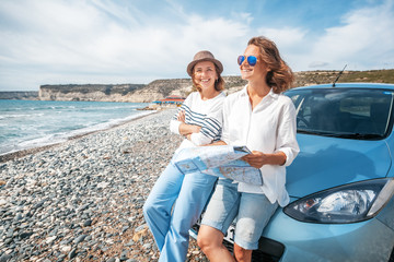 Two young beautiful female friends travel together by car, look at the road map against the sea, vacation, happiness, navigation, map