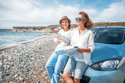 Two young beautiful female friends travel together by car, look at the road map against the sea, vacation, happiness, navigation, map - 196989307