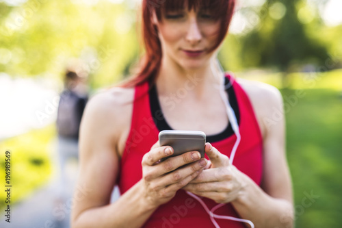 Young athlete in park holding smart phone, listening to music.