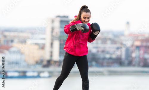 Young girl wearing boxing gloves throwing a punch - martial arts training