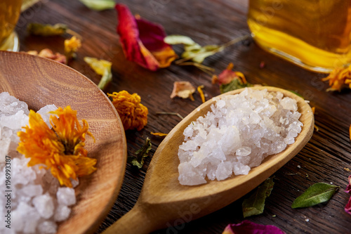 SPA concept: composition of spa treatment with natural sea salt, aromatic oil and flowers on wooden background © Aleksey